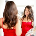 Woman trying clothing looking in mirror